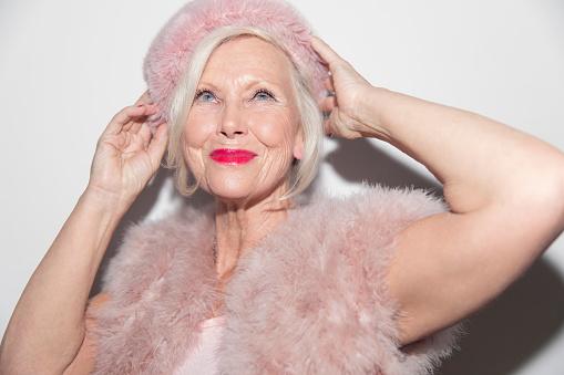 Portrait confident, glamorous senior woman wearing pink fur